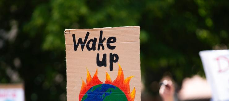 A protester holding a sign of a burning earth saying 'wake up'.